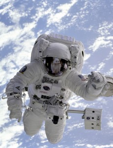 The pale blue Earth serves as backdrop for astronaut Michael Gernhardt during his Extravehicular Activity (EVA). He is standing on a Manipulator Foot Restraint (MFR) attached to the Remote Manipulator System (RMS). He is positioned over the Payload Bay and Endeavour's forward section is reflected in his visor. A thermal cube is attached to the RMS and records temperatures during spacesuit evaluations. Unlike earlier spacewalking astronauts, Gernhardt was able to use an electronic cuff checklist, a prototype developed for the assembly of the International Space Station (ISS).